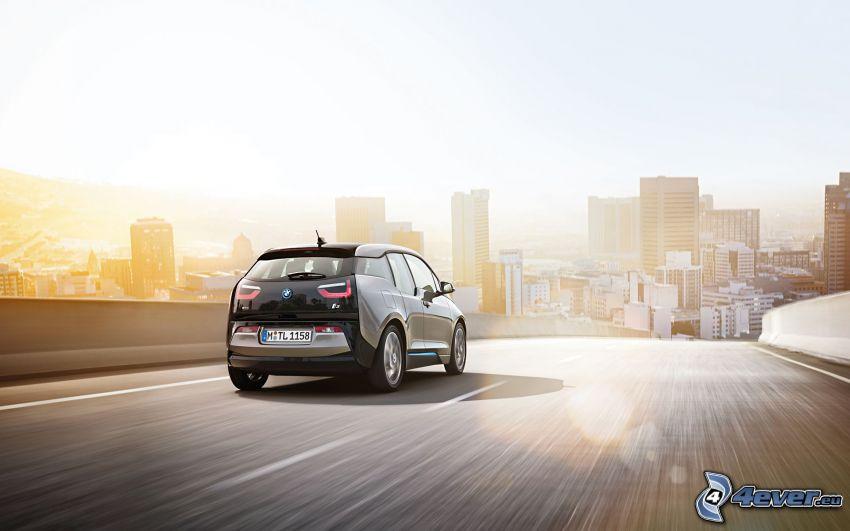 BMW i3, camino, puesta de sol sobre la ciudad