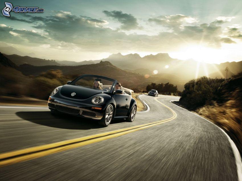 Volkswagen New Beetle Cabrio, puesta de sol sobre la carretera, sierra