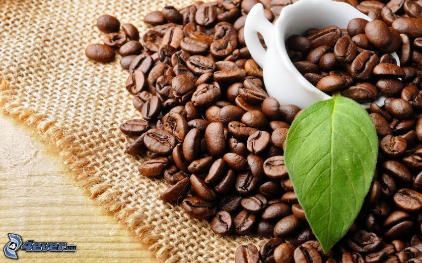 granos de café, taza, hoja verde