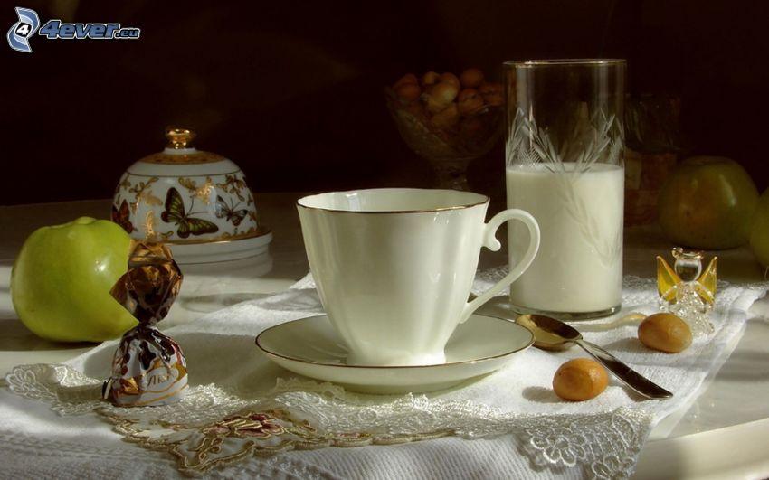 taza de té, leche, manzana verde, caramelos