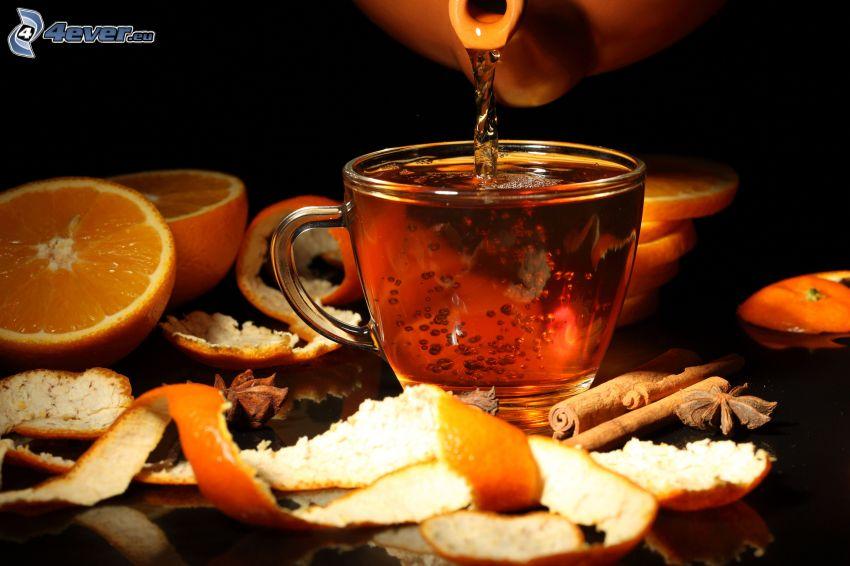 taza de té, naranjas en rodajas, canela