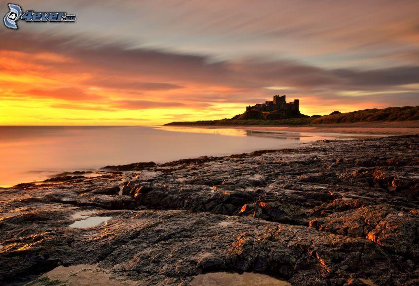 Bamburgh castle, después de la puesta del sol, playa rocosa