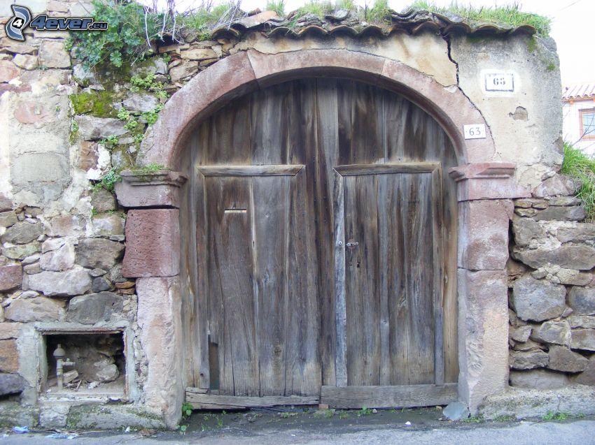 puerta de madera, muro de piedra