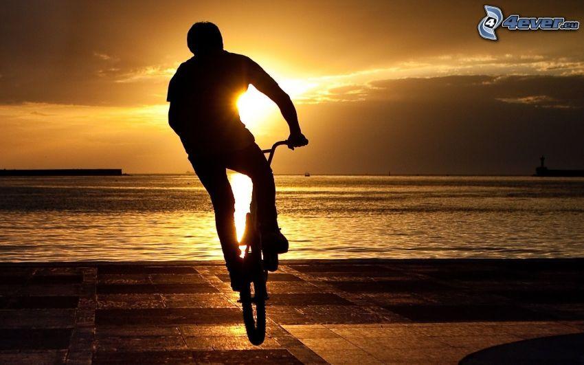 ciclista, puesta de sol sobre el mar, silueta