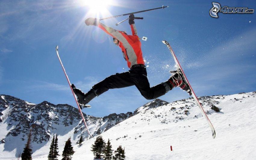 salto con esquís, esquiador, colinas cubiertas de nieve, árboles coníferos, cielo azul, sol, acrobacia