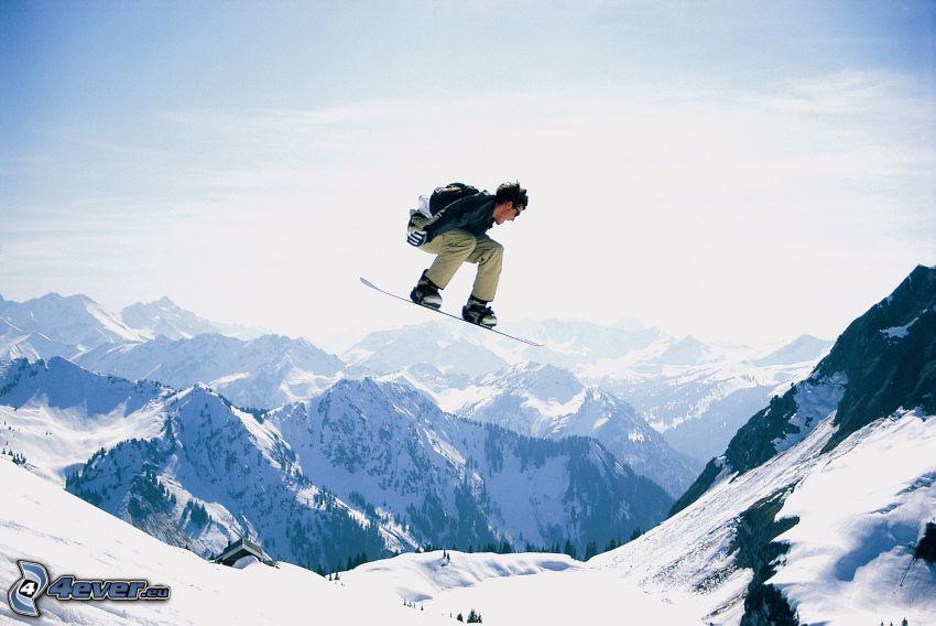 salto en tabla de snowboard, montañas nevadas