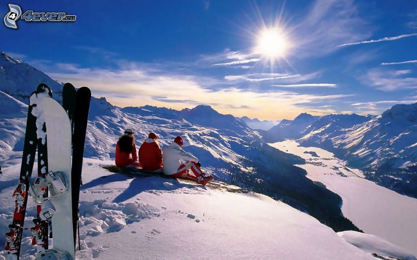 Snowboarders, esquiadores, montañas nevadas, sol