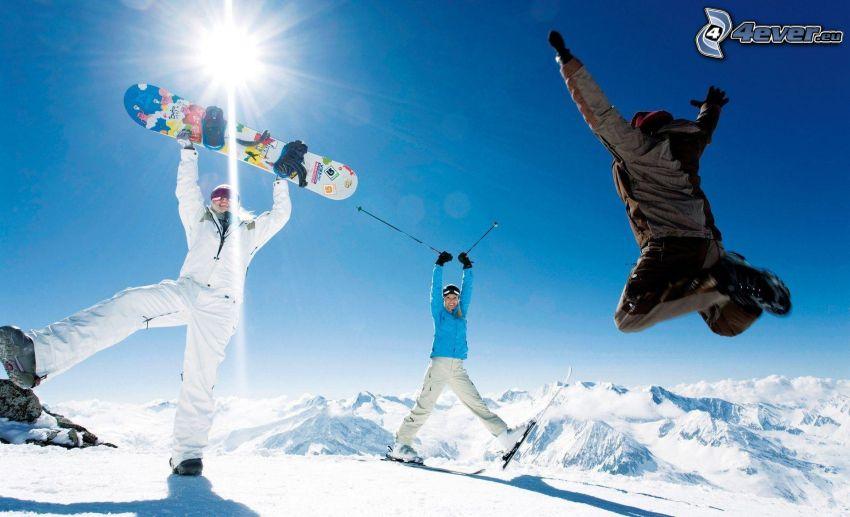 Snowboarders, salto, colinas cubiertas de nieve