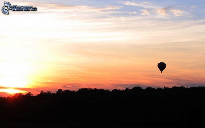 globo de aire caliente, siluetas de los árboles, cielo anaranjado
