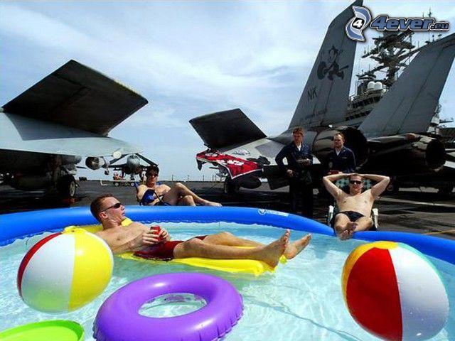 chico en la piscina, relajarse, relax, aviones de caza, portaaviones