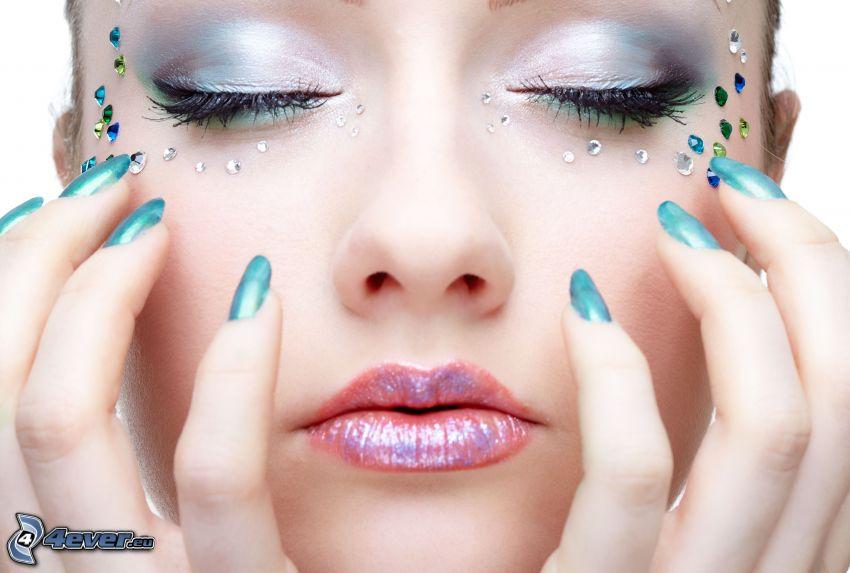mujer con maquillaje, brillo de labios, uñas pintadas