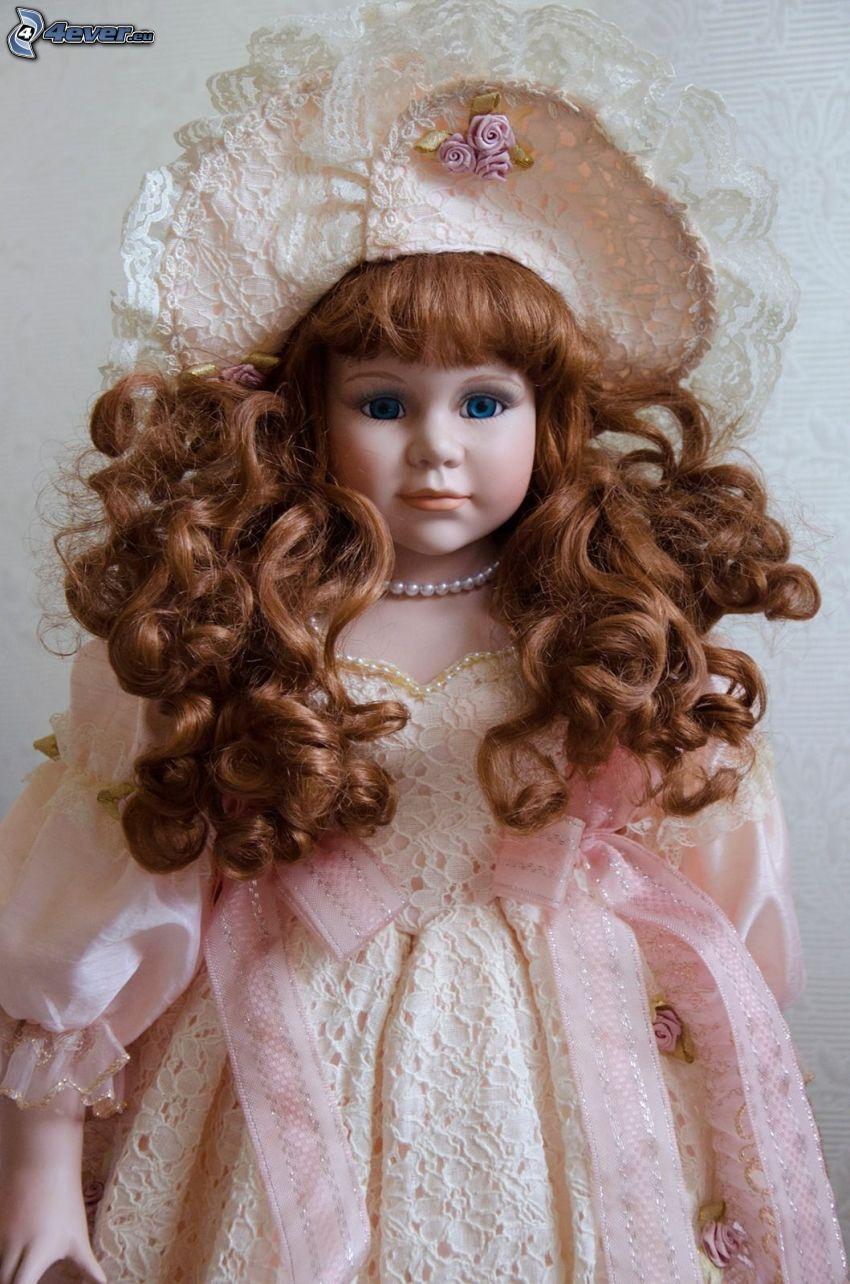 muñeca de porcelana, vestido de color rosa, cabello rizado