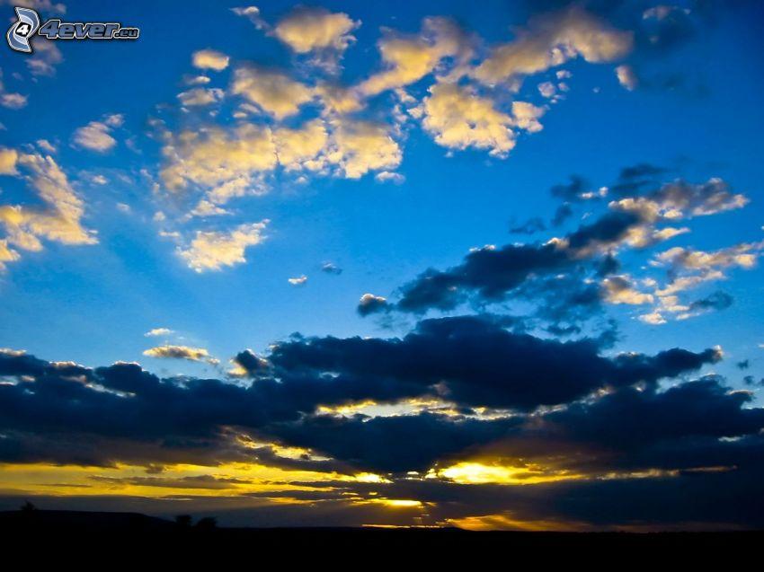 atardecer oscuro, el sol detrás de los nubes
