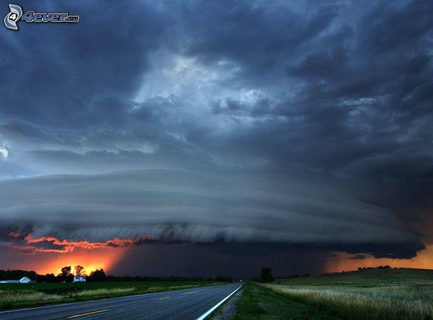 Nubes de tormenta, después de la puesta del sol, camino recto, campo
