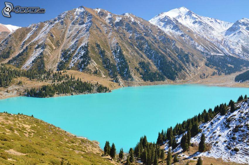 Kolsai Lakes, lago de montaña, colinas cubiertas de nieve