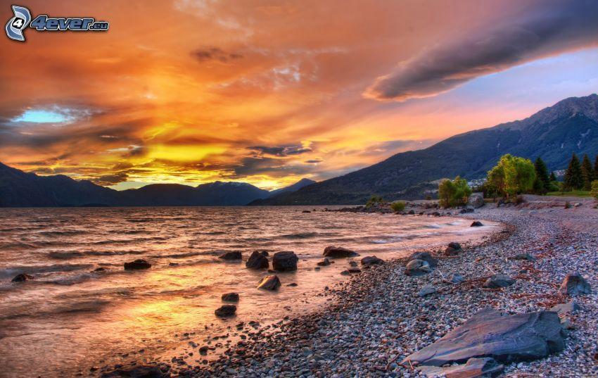 lago, playa rocosa, después de la puesta del sol, cielo anaranjado