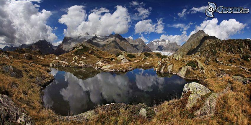 lago de montaña, montañas rocosas, hierba seca, nubes