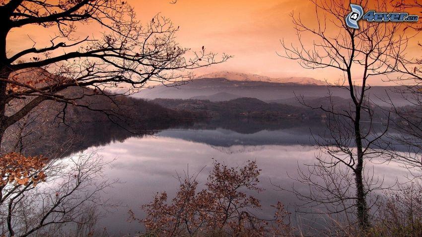Lago en el bosque, cielo anaranjado, árboles