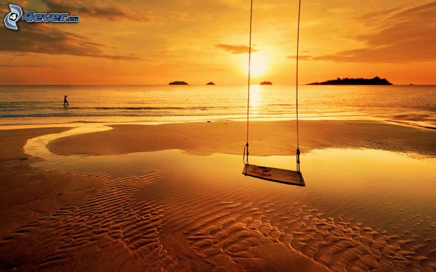 columpio, puesta de sol sobre el mar, playa de arena, cielo anaranjado