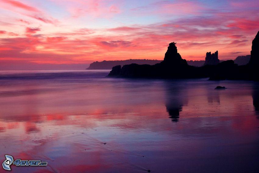 costa rocosa, cielo púrpura