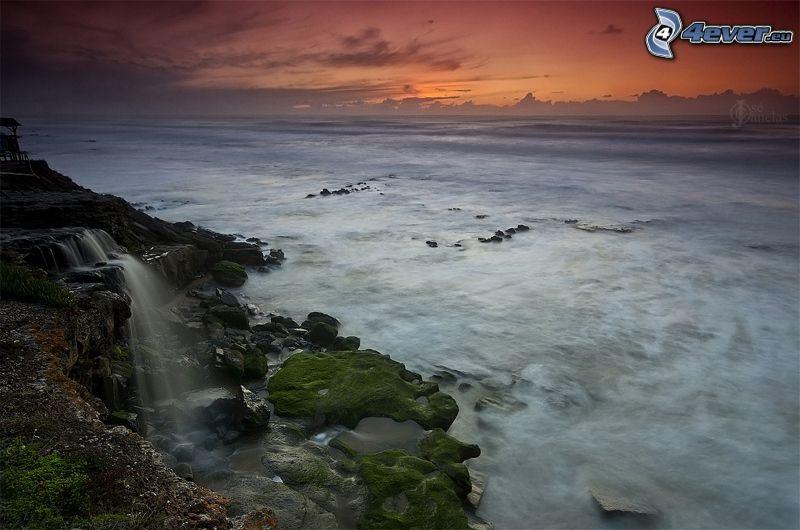 costa rocosa, mar, cascada, después de la puesta del sol