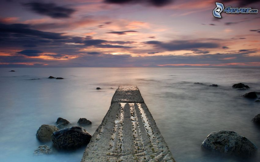 muelle, rocas en el mar, después de la puesta del sol