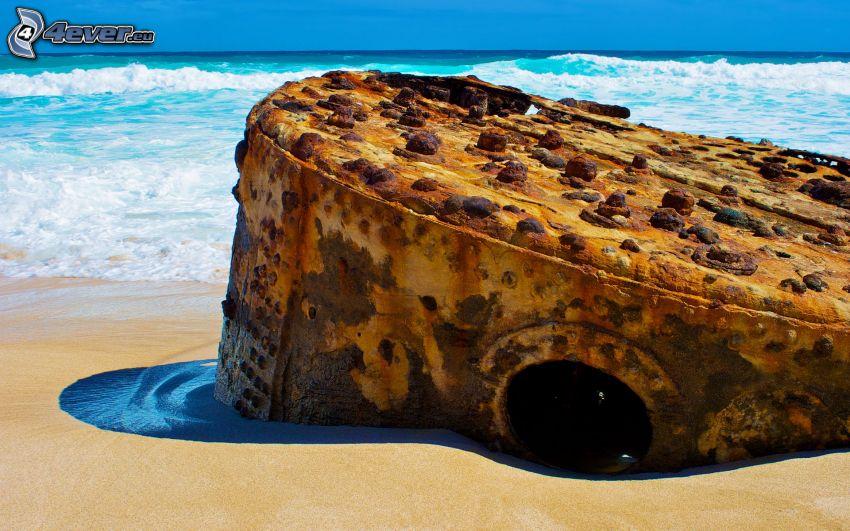 Nave abandonada oxidada, playa de arena, mar