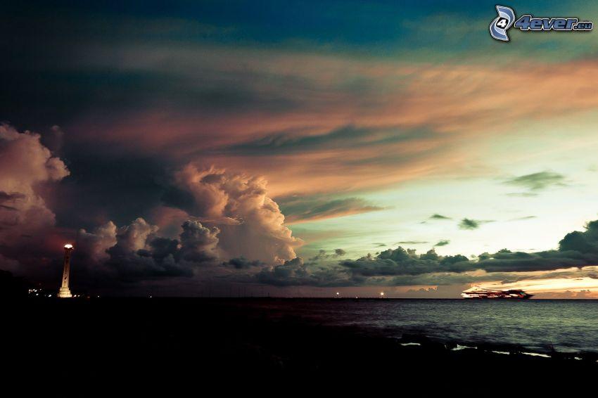 Nubes de tormenta, puesta de sol en el mar, playa de noche