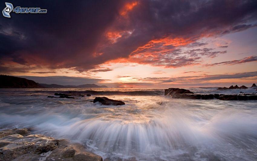 olas en la costa, puesta de sol sobre el mar, nubes oscuras