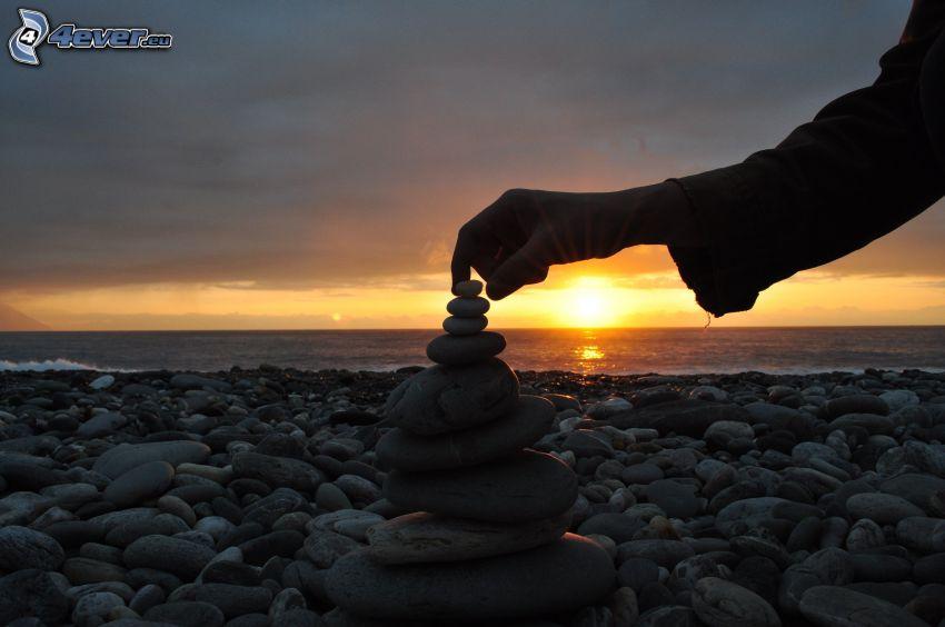 playa rocosa, puesta de sol sobre el mar, mano