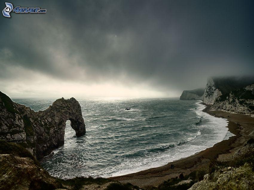 puerta rocosa en el mar, costa rocosa, mar turbulento, cielo oscuro
