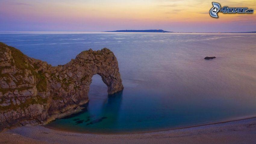 puerta rocosa en el mar, playa, cielo de la tarde