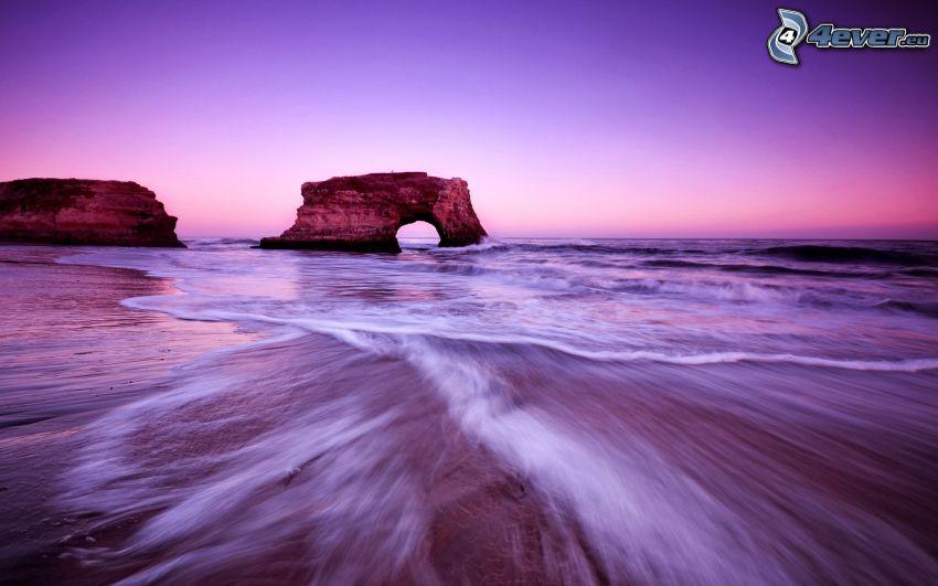 puerta rocosa en el mar, playa, cielo púrpura
