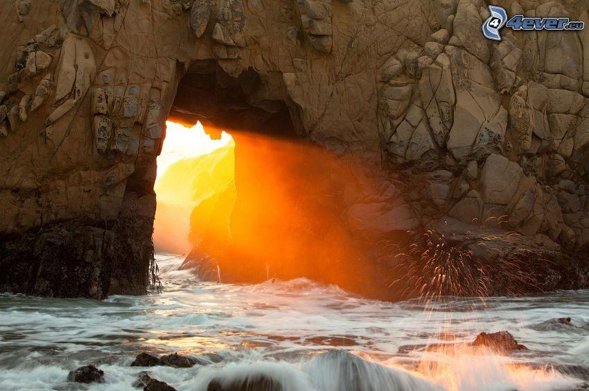 puerta rocosa en el mar, rayos de sol