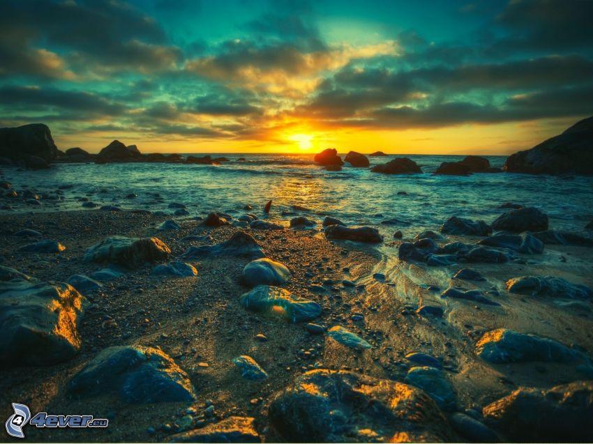 puesta de sol en el mar, costa de piedra