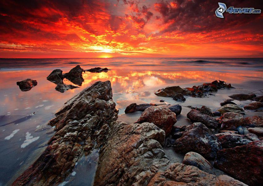 puesta de sol en el mar, costa rocosa, cielo rojo