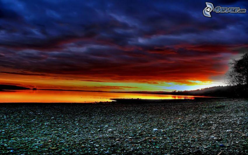 puesta de sol en el mar, costa rocosa, nubes