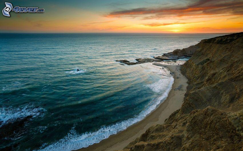 puesta de sol en el mar, costa rocosa, vista al mar
