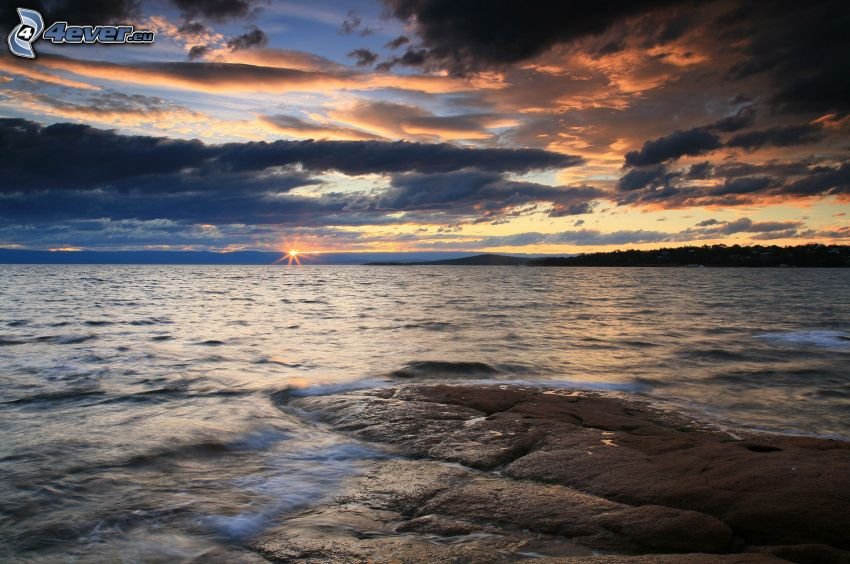 puesta de sol en el mar, nubes oscuras