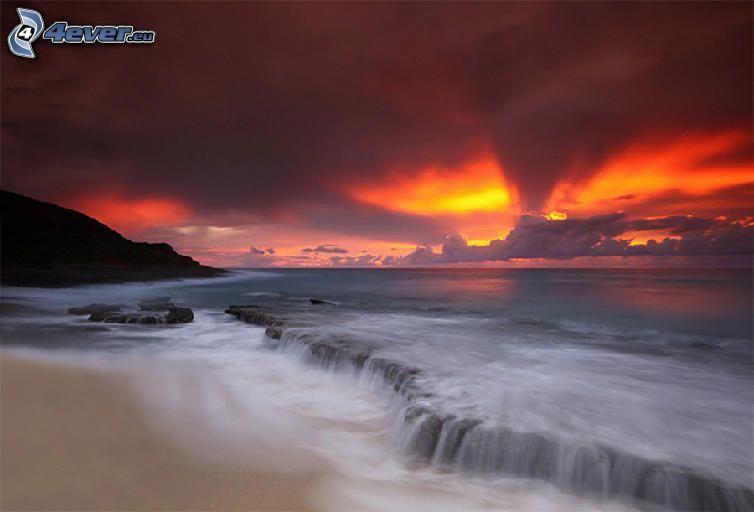 puesta de sol naranja sobre el mar, nubes, playa de arena