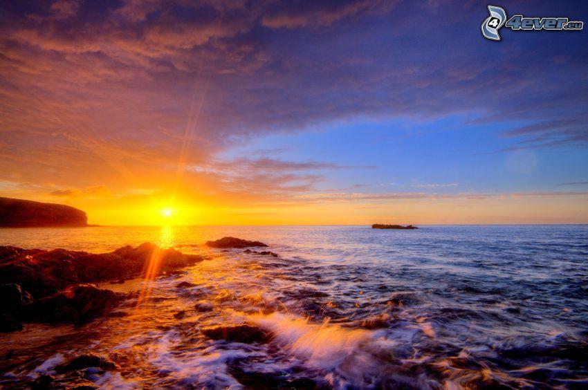 puesta de sol sobre el mar, cielo de la tarde, costa de piedra