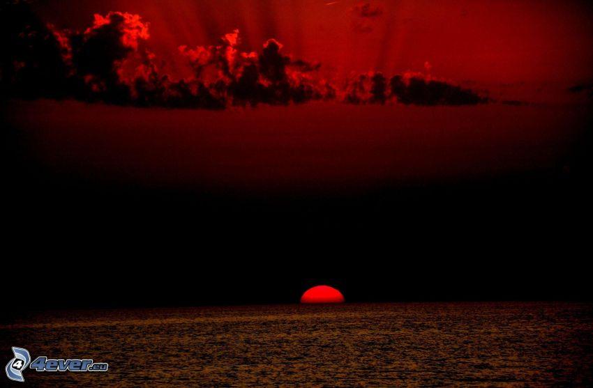 puesta de sol sobre el mar, cielo rojo