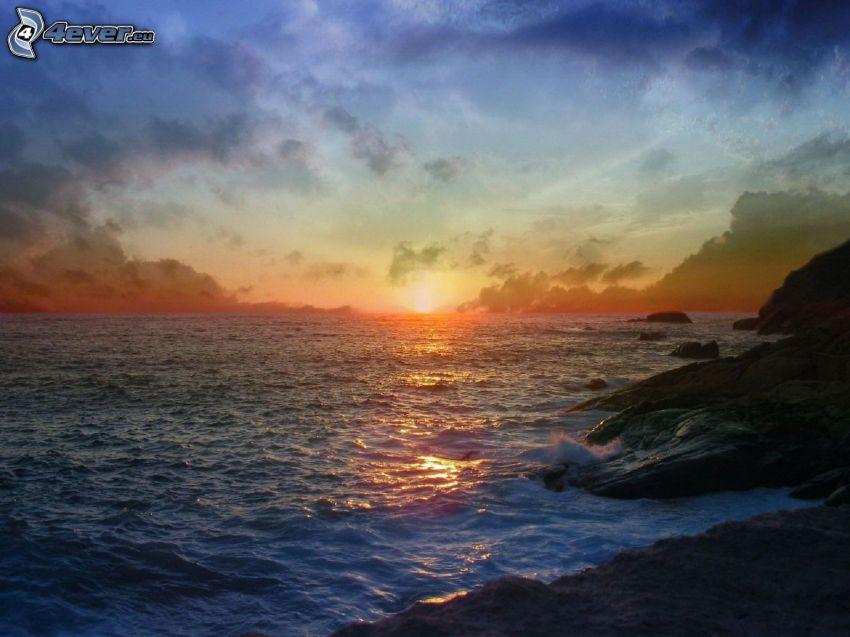 puesta de sol sobre el mar, costa de piedra, cielo