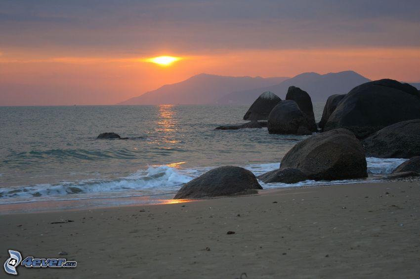 puesta de sol sobre el mar, costa de piedra