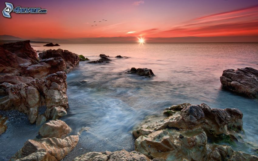 puesta de sol sobre el mar, costa rocosa