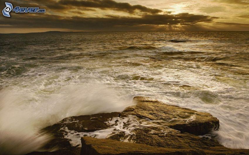 puesta de sol sobre el mar, el sol detrás de los nubes, roca