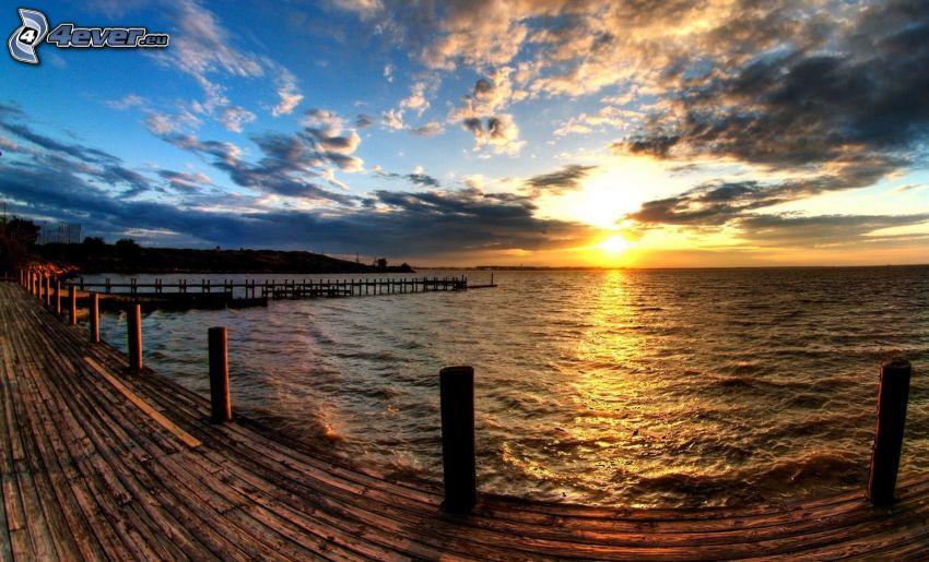 puesta de sol sobre el mar, nubes, muelle de madera