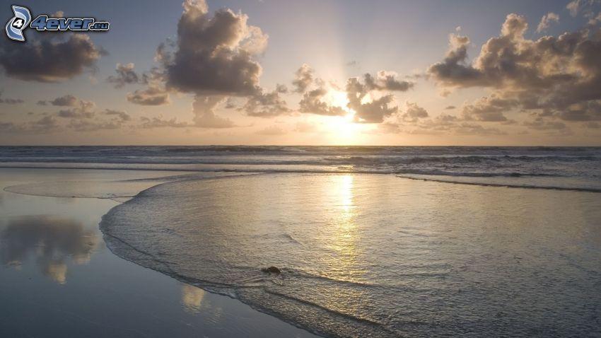 puesta de sol sobre el mar, playa, nubes