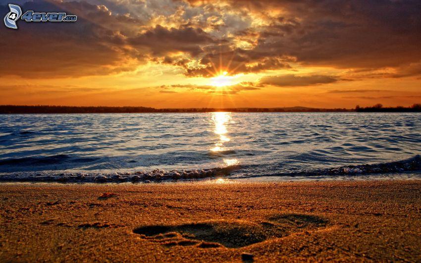puesta de sol sobre el mar, playa de arena