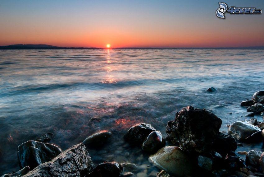 puesta de sol sobre el mar, playa rocosa